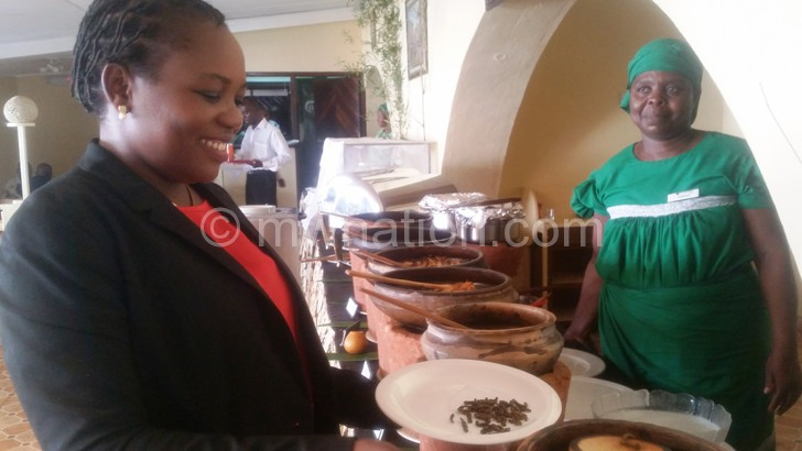 A diner scoops a spoonful of mphalabungu over a traditional lunch at Sunbird Lilongwe