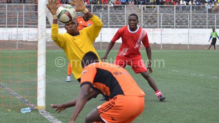 Songani's keeper Allan Chinyama (in yellow) keeps out  Wadabwa's(back to camera) attempt