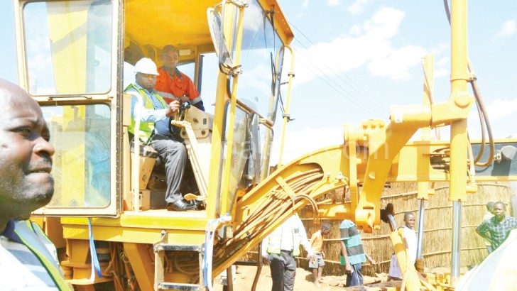 Let the works begin: Nankhumwa rides the grader at the launch
