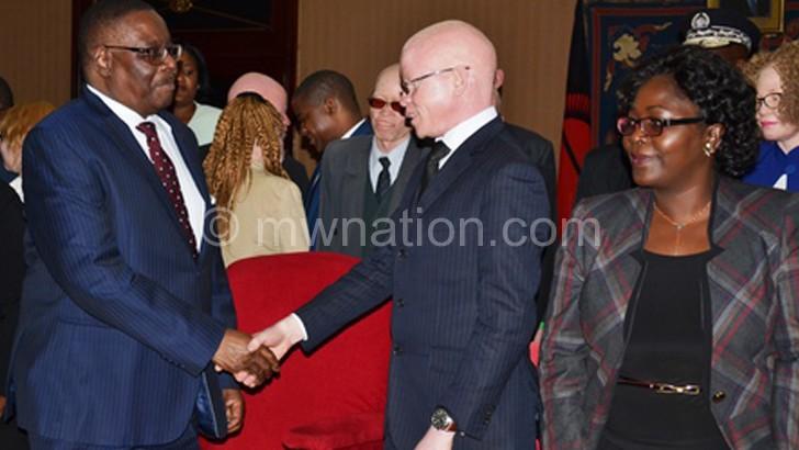 Mutharika greets Apam president Boniface Massa during the meeting