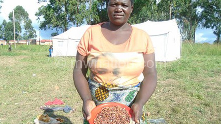 A woman shows off the rotten beans distributed at the camp