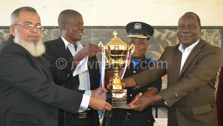 Regional executive committee for community policing forums chair Muhammad Kasmany (L) and Chigwenembe present the trophy to Kadzayekha