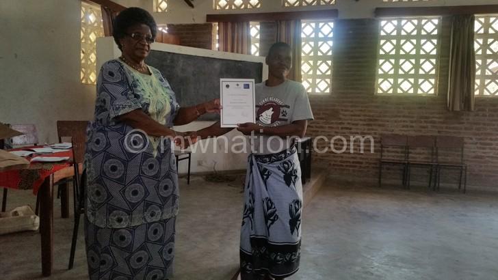 Nhlema (L) giving a certificate to Mankhamba (R)