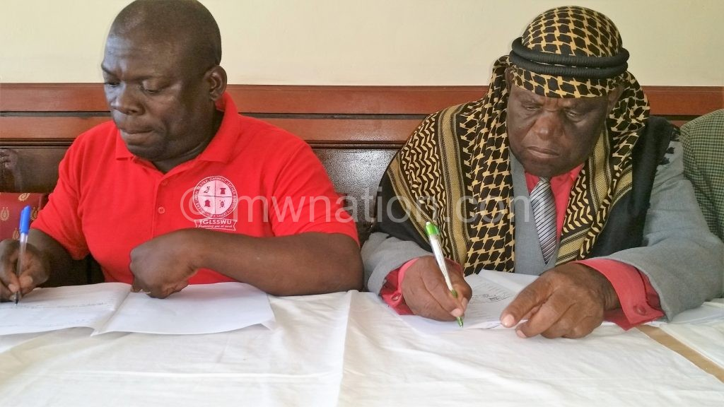 Nasimba (R) and Chiwaya sign the MoU
