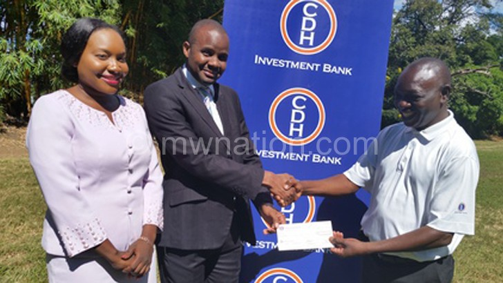 CDHIB's Chowawa (C) presents the cheque to Kaira (R) as Chipezaani looks on