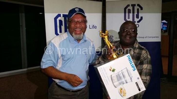 Nico Life's Karim (L) presents a trophy to Mhango