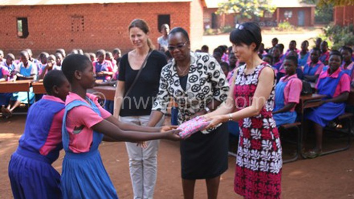 Nevin (R) and colleagues presenting the packs to some of the beneficiaries