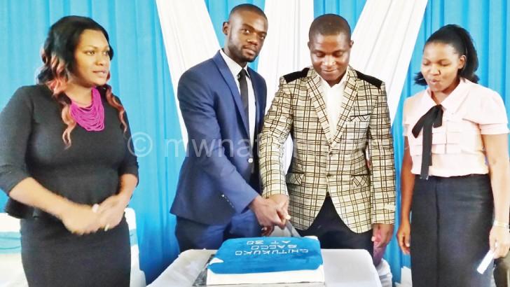 Kondowe (2nd L) and Mkonda cut the cake as other members look on