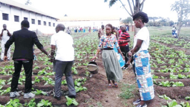 The visiting group helps inmates to water vegetables