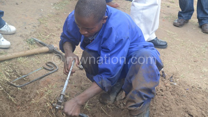 A BWB technician uprooting one of the illegal connections in an earlier operation