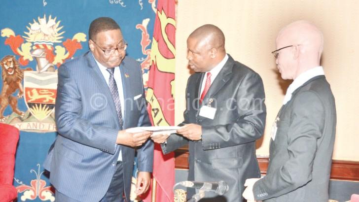 Muchena (C) hands the report to Mutharika as Massa looks on