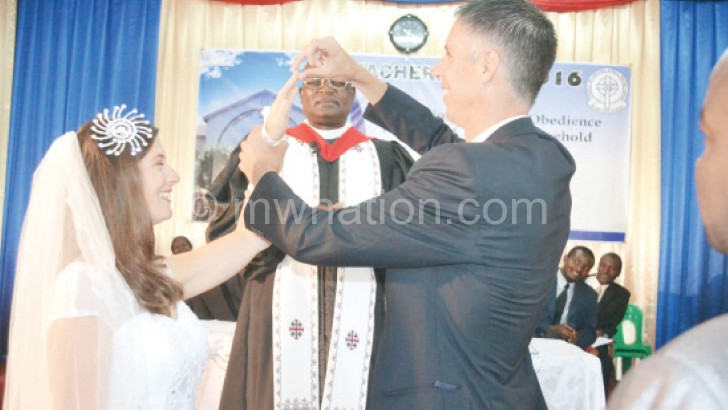 The Reverend Joel (R) puts a ring on Rabecca's  finger during the mock wedding