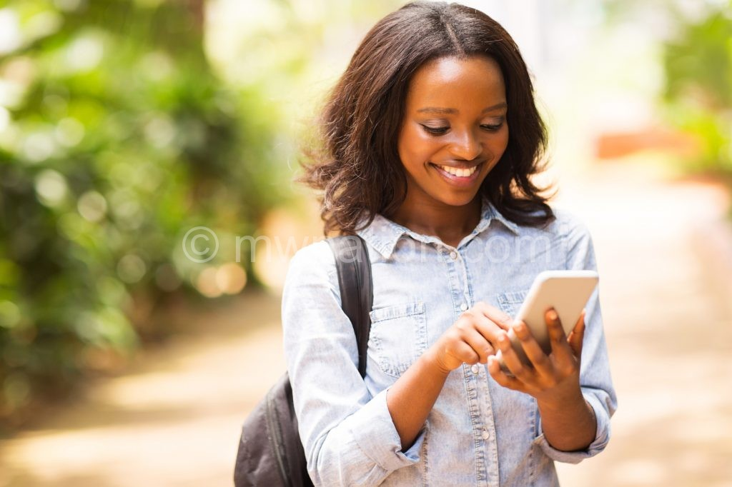 happy young african american uni student using cell phone