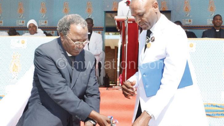 Church elder Ulemu Chilapondwa (R) helps Sasu cut the ribbon during the launch