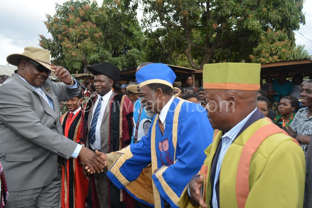 Mutharika shakes hands with T/A Kapeni as others look on