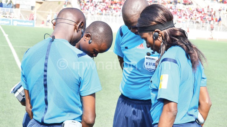 Kwimbira (R) prays with male colleagues ahead of a big mattch