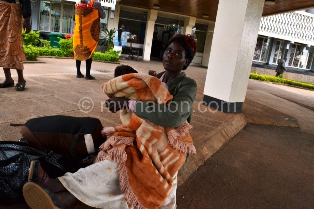 A teacher nursing her child at dusk while preparing to spend the night at the Capital Hill