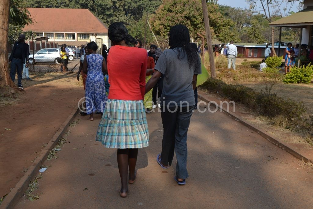 Out on bail: Some of the KCN students walk backwards to their  freedom to avoid cameras