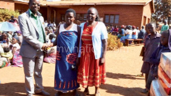 Mhango (C) shakes hands with Namakhwa as Kunje (R) looks on