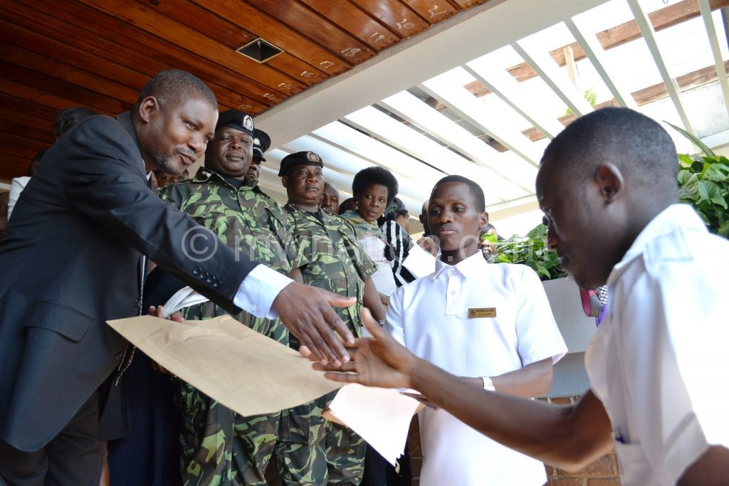 Nyson Sekani hands over petition to Lilongwe DC Charles Makanga as Union vice president Iron Kathonyeza looks on