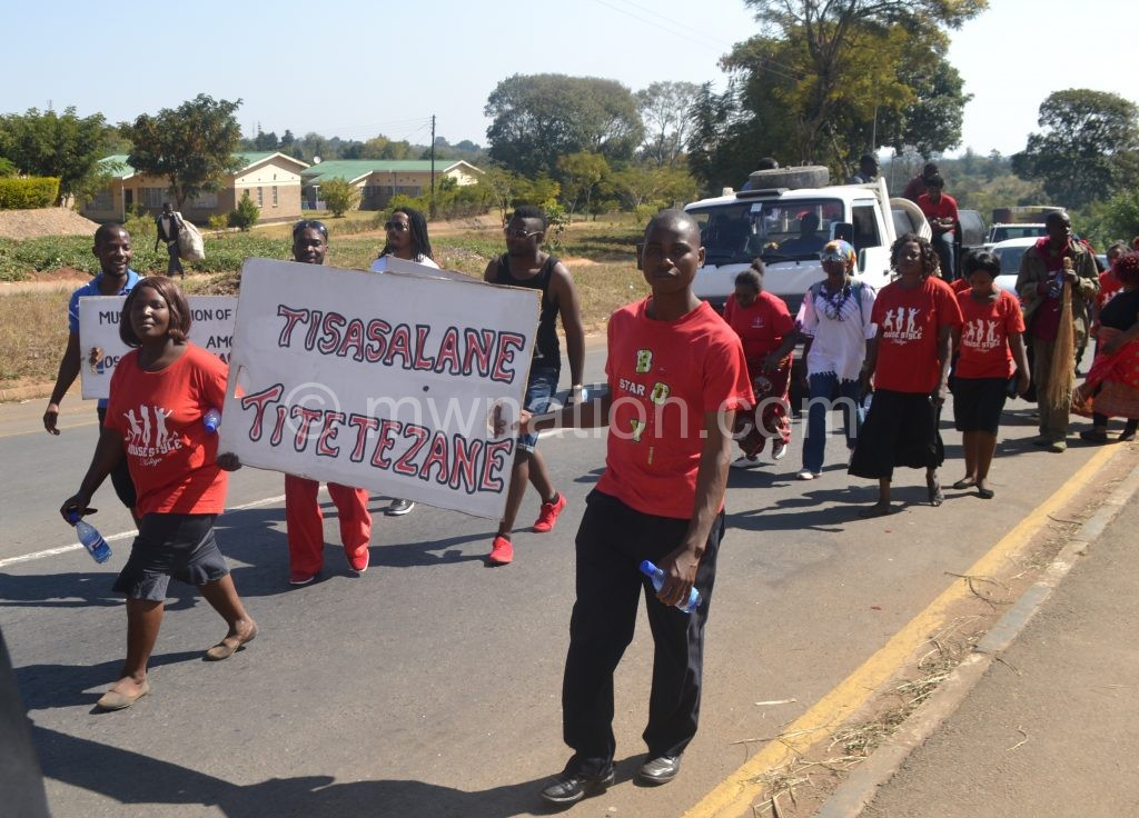 The musicians hoist a placard during the march in Blantyre