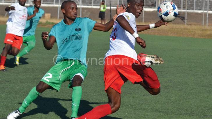 Take that: Bullets defender Miracle Gabeya (R) flicks the ball over Mafco's Chikondi Maloya