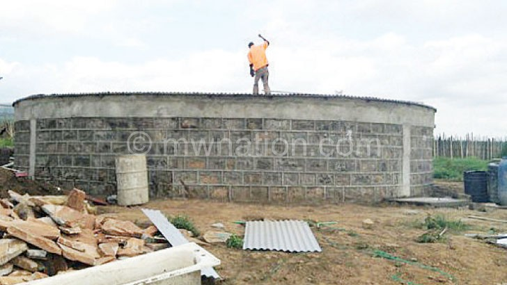 African Water Bank technicians put the final touches on a water storage tank at a homestead in Narok County, Kenya