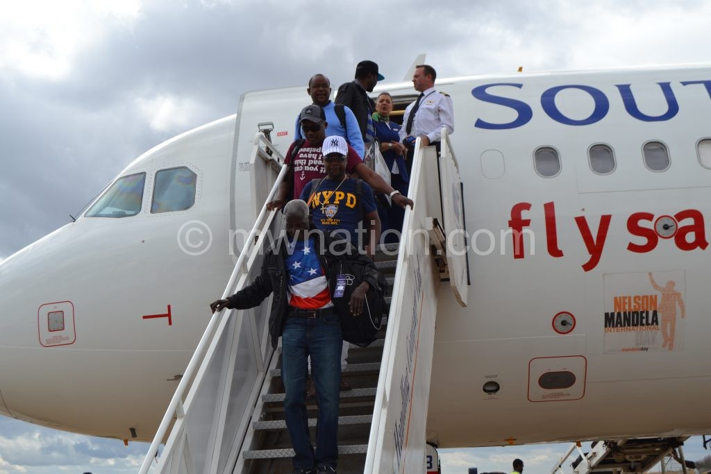 Giddes leads his team in alighting from the plane