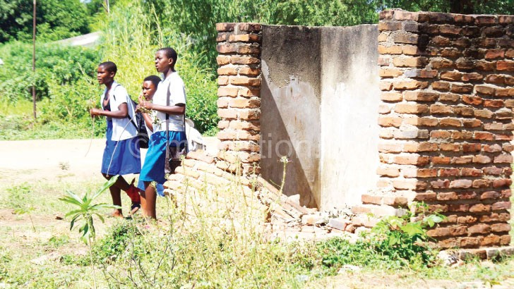 Girls walking out of what used to be their latrine before the new ones were built
