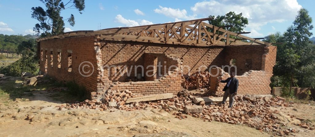Pastor Chigwenembe pointing at the partly demolished church