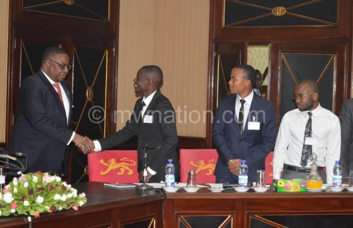 Mutharika greets the students' at the start of the meeting