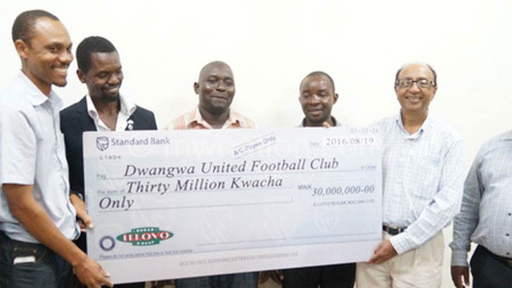 Bachan (R) presents the cheque to the club officials