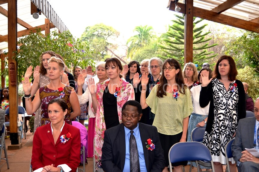 The volunteers stand behind Magwira (seated, R) as they take oath