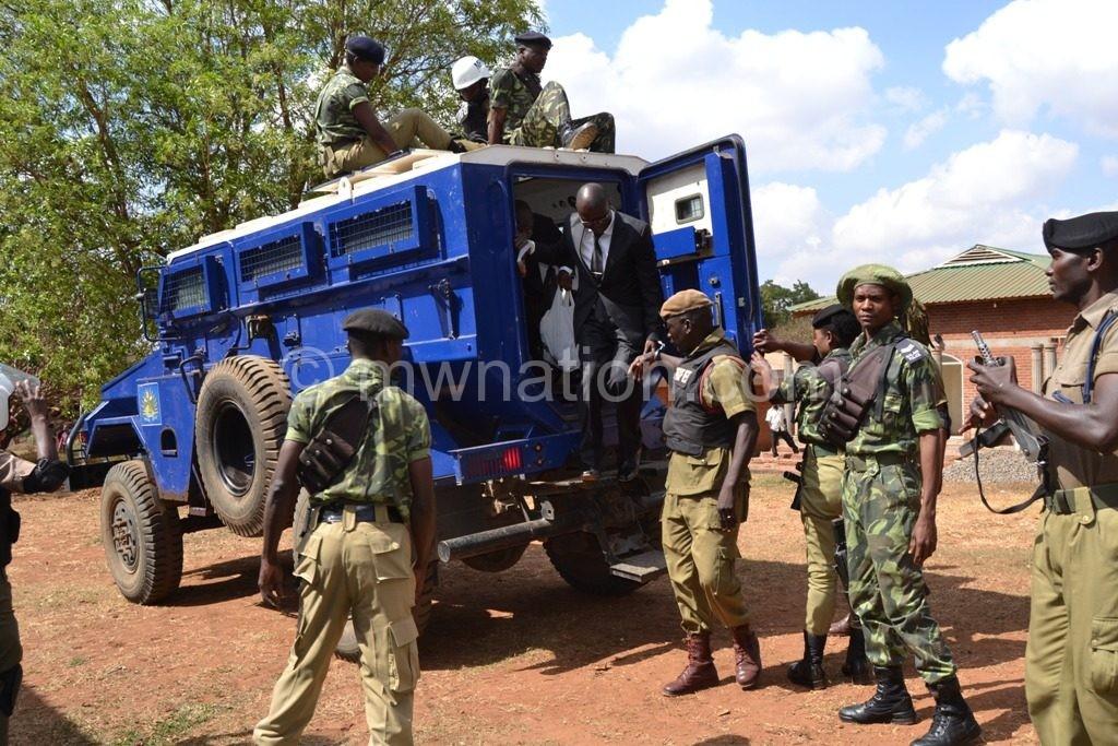 Kasambara disembarks from the armoured police van before the sentencing