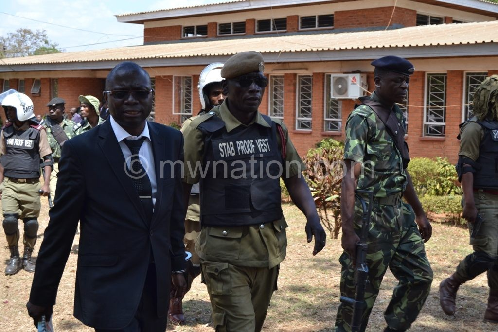 Kasambara heads for the police van after the sentencing