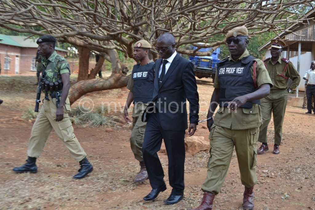 Kasambara (in suit) captured in police escort during the trial period