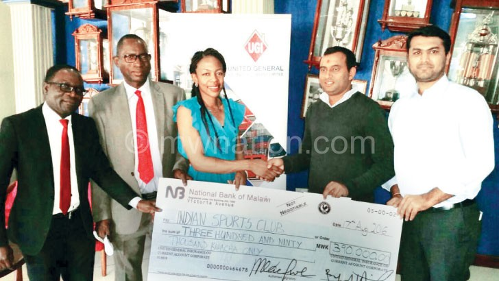 Mangochi (C) presents a symbolic cheque to Patel (2ndR)as Chikuse (2ndL),  Singano (L) and Shah look on