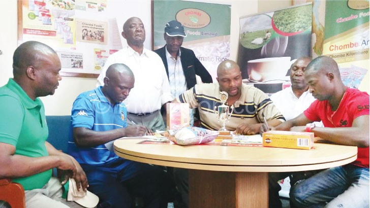 Masamba (R) and Kayuni (2ndL) sign contracts as Chitenje (3rdR), Kapalamula (L) and other officials look on