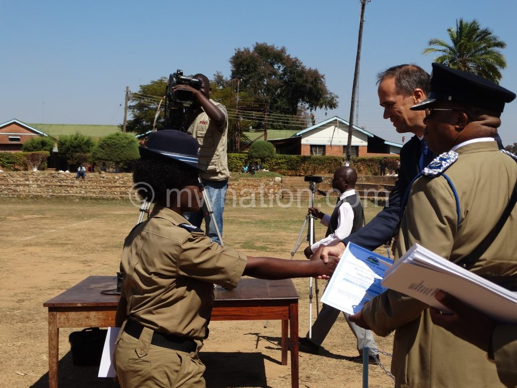 A female police prosecutor (L) shakes hands with Germann before she receives her certificate