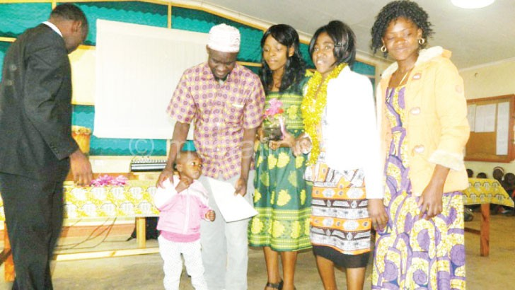 A tailoring graduate poses with his family after receiving his certificate from Chirwa