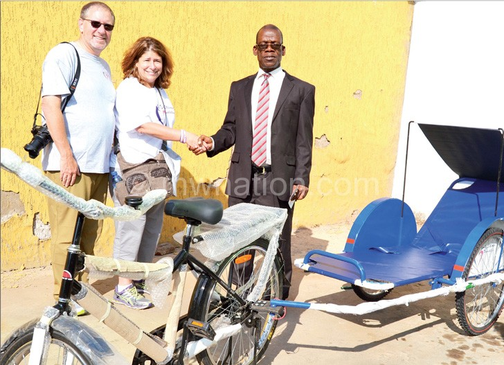 NPL Deputy Chief Executive Officer Alfred Ntonga receives one of the two bicycle ambulances from the Stillman's