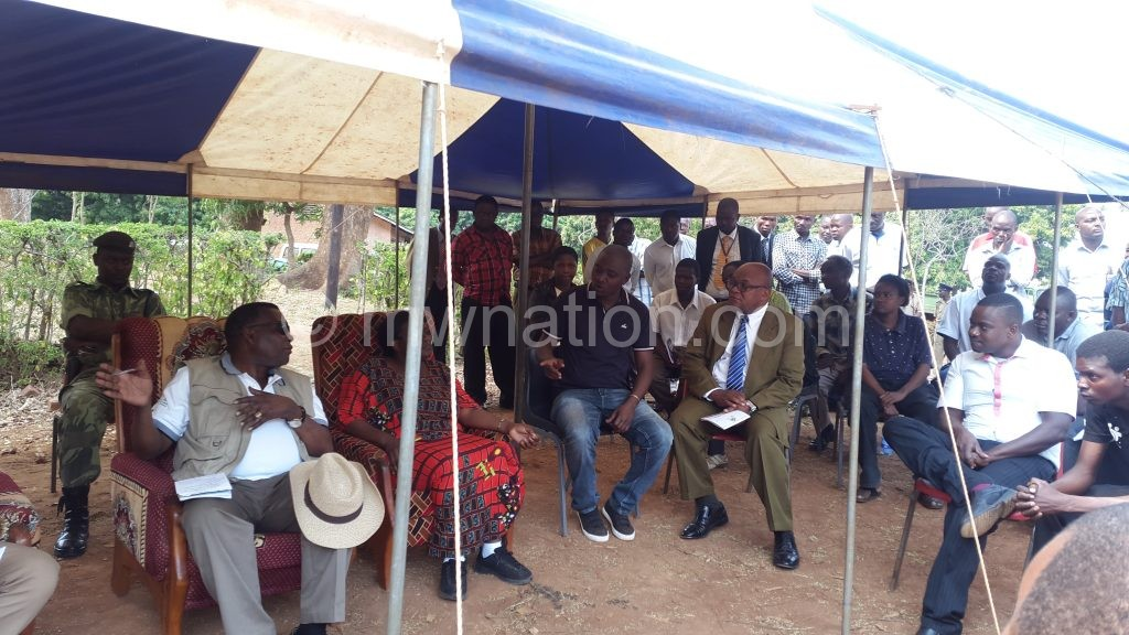Chaponda (Front L) tries to reason with the group's representatives as the villagers chanted in protest nearby