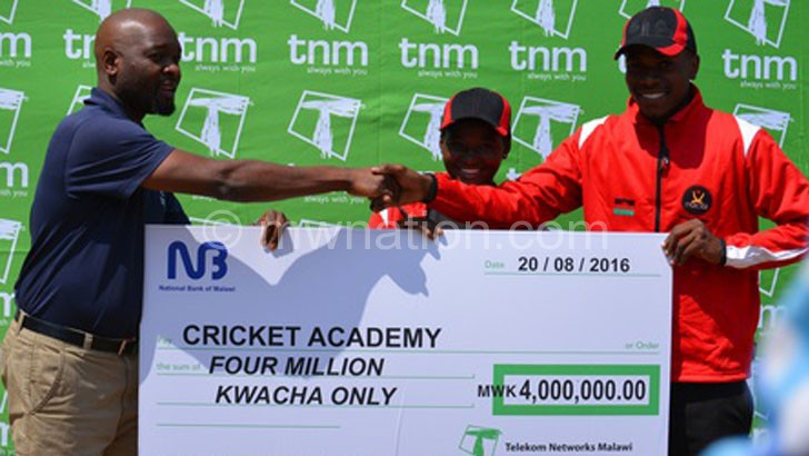 Nsapato (L) presenting a symbolic cheque to academy coach Gracian Ntambalika as Hussen (C) looks on