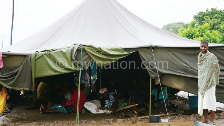 Flood victims find shelter in a tent as they wait for relocation