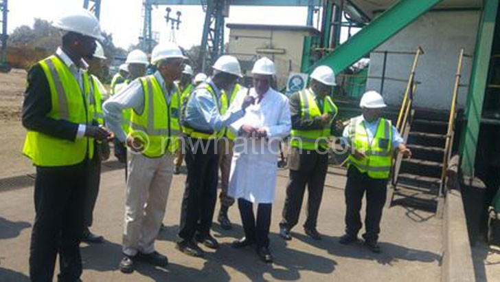 Mwanamvekha (in white coat) listens as an Illovo official takes him through the suagr milling process