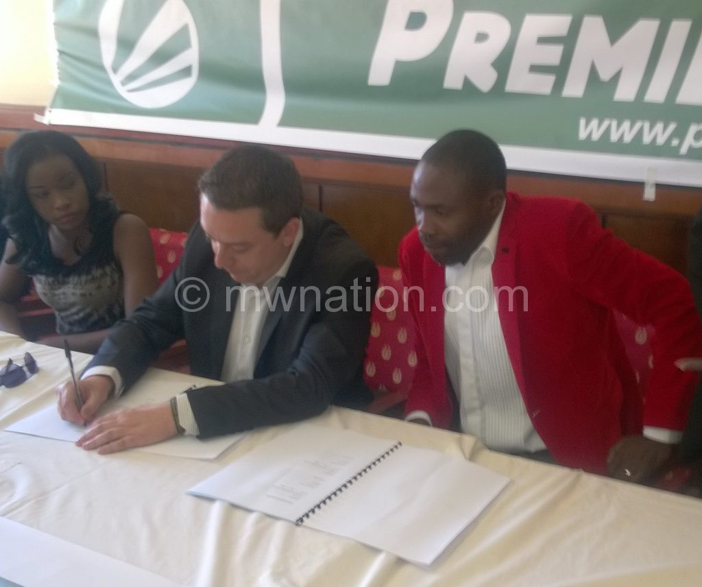Mponda (R) and Morales putting pen to paper