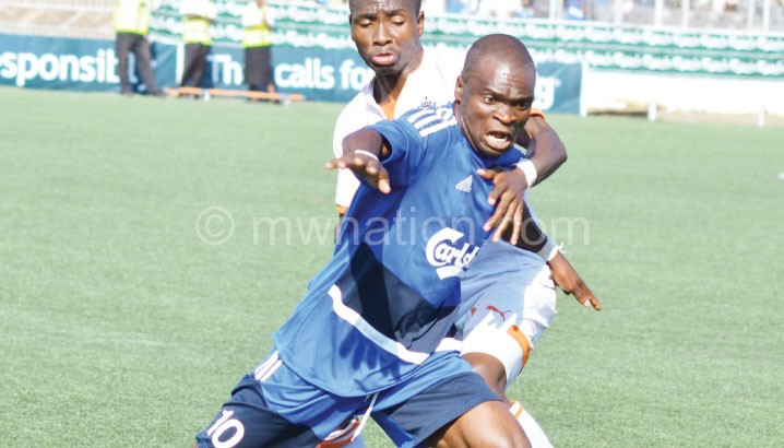 Mangochi Police's Charles Douglas (in blue) tries to beat Wanderers' Mike Kaziputa in the semi-final