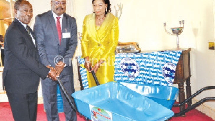 Mwanza (L) and Mtegha (C) make a symbolic presentation of assorted items to Mutharika
