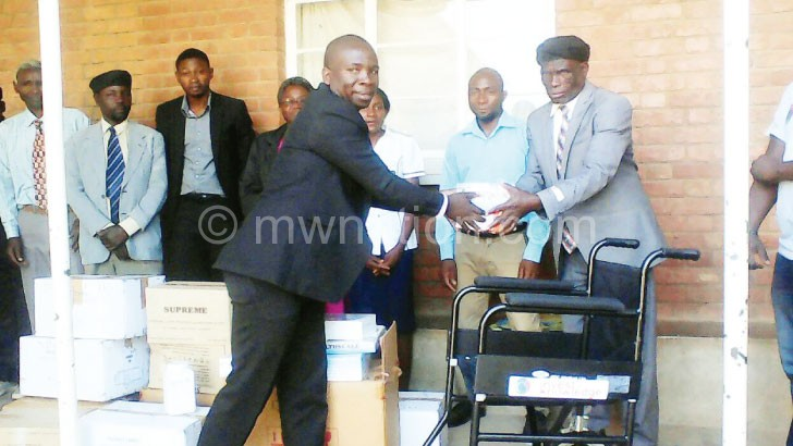 Mkandawire (left) making a symbolic presentation of the drugs to T/A Mwahenga