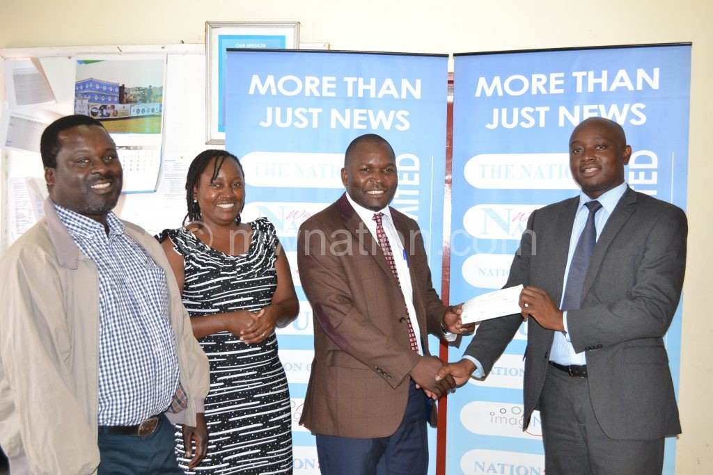 Kadewa (R) receiving the cheque from Phiri as Beatric Butao and Leonard Kamuba (L) look on